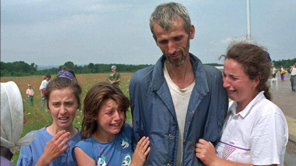 FILE - In this Monday July 17, 1995 file photo, Bosnian refugees cry as their father and husband arrives at the U.N. air base in Tuzla, Bosnia, after he survived the death march of six days from Srebr
