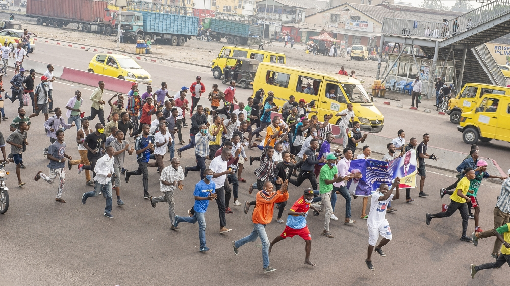 Demonstrators run in the street during a protest where demonstrators and police officers clashed in Kinshasa on July 9, 2020 in demonstrations organized against the presidential party Union for Democr