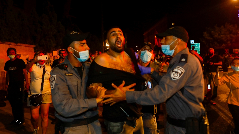 ISRAEL-POLITICS-PROTEST  A protester is detained by Israeli police during a demonstration against Israeli Prime Minister Benjamin Netanyahu outside his official residence in Jerusalem
