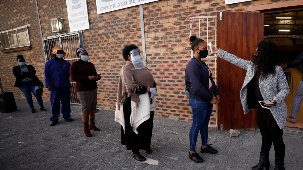 Teachers practice social distancing before being screened after the coronavirus disease (COVID-19) lockdown in Cape Town
