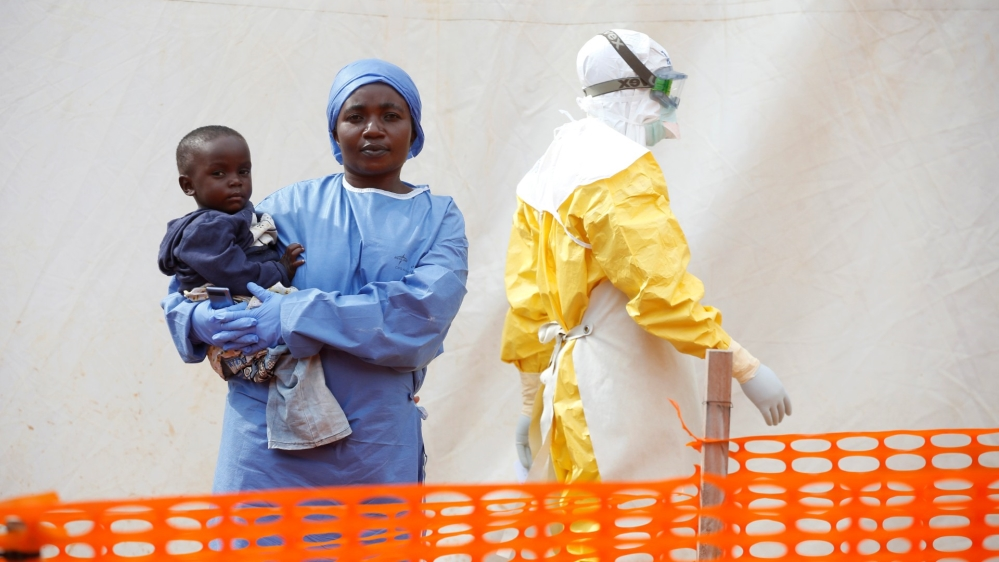 FILE PHOTO: Mwamini Kahindo, an Ebola survivor working as a caregiver to babies who are confirmed Ebola cases, holds an infant outside the red zone at the Ebola treatment centre in Butembo