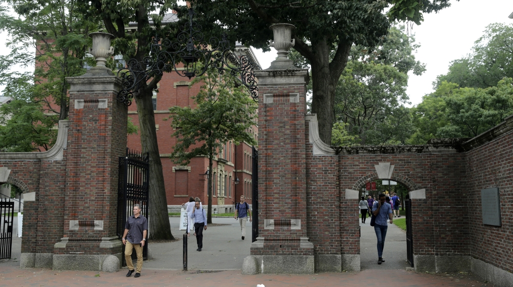 Pedestrians walk through the gates of Harvard Yard at Harvard University in Cambridge, Mass., Tuesday, Aug. 13, 2019. (AP Photo/Charles Krupa)