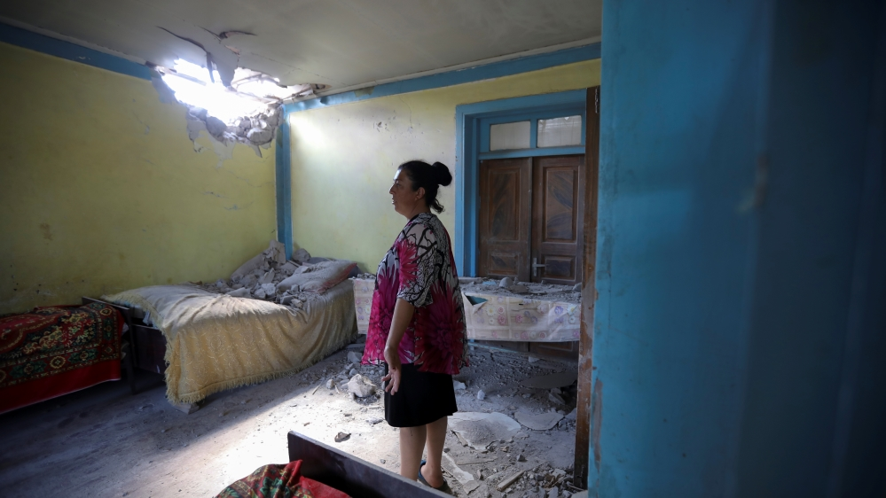 A woman stays in a house damaged by a recent shelling in armed clashes on the border between Azerbaijan and Armenia, in the village of Dondar Quschi