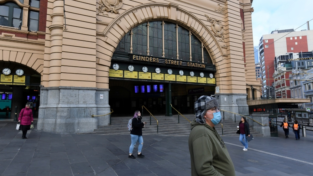 People are seen outside of Flinders Street Station during morning peak hour as the city is in lockdown in Melbourne