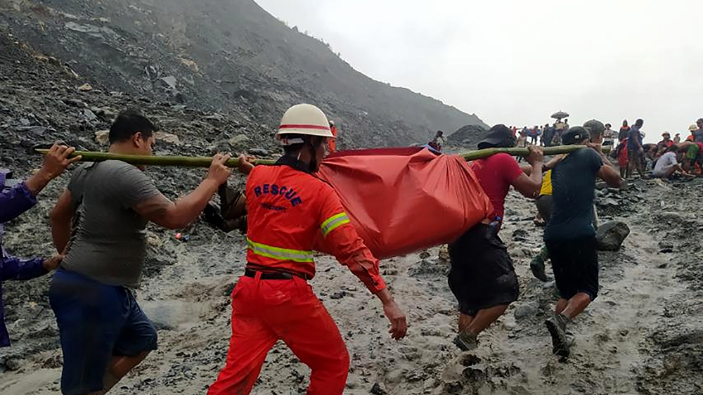 epa08522227 A handout photo made available by the Myanmar Fire Services Department shows rescue workers carrying the body of a victim after a landslide accident at a jade mining site in Hpakant, Kachi