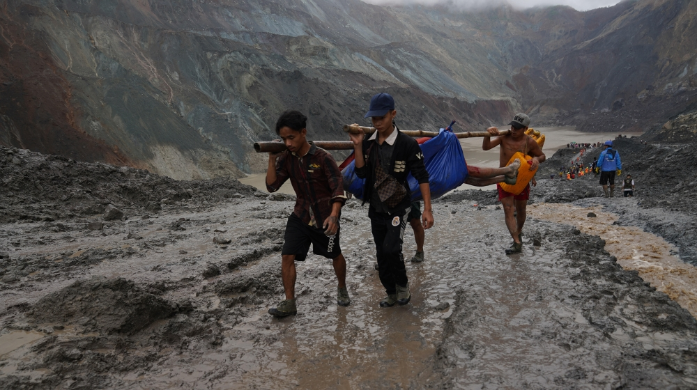 Rescuers recover a body near the landslide area in the jade mining site in Hpakhant in Kachin state on July 2, 2020. The battered bodies of more than 120 jade miners were pulled from a sea of mud afte