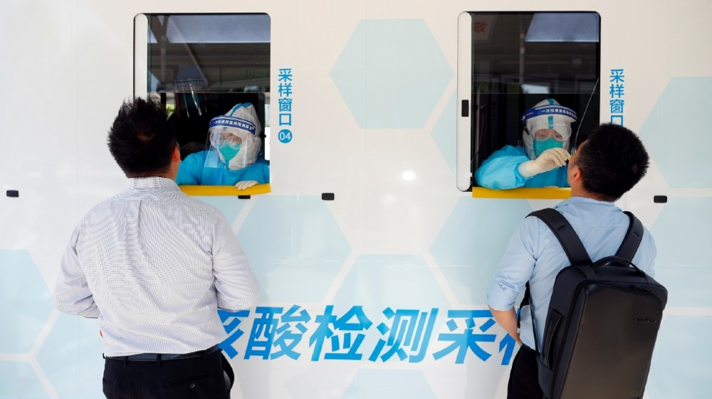 Two people are tested at the windows of a testing vehicle, following a new outbreak of the coronavirus disease (COVID-19) in Beijing, China, June 30, 2020. REUTERS/Thomas Peter