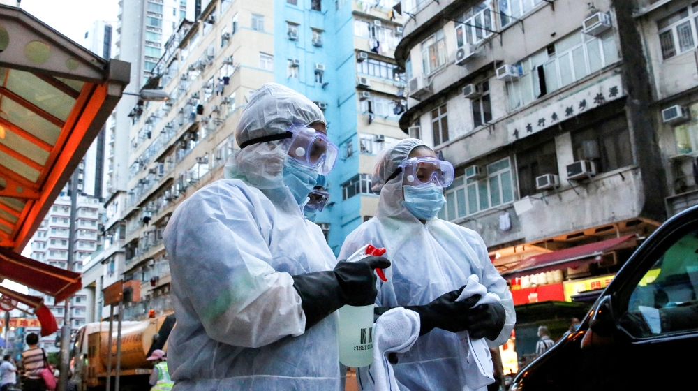 Cleaning workers wearing protective gear walk past a wet market following the coronavirus disease (COVID-19) outbreak at Sham Shui Po, one of the oldest districts in Hong Kong, China July 17, 2020. RE