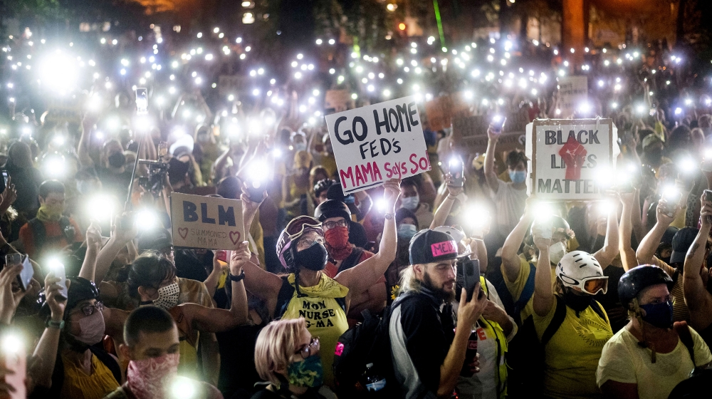 Hundreds of Black Lives Matter protesters hold their phones aloft on Monday, July 20, 2020, in Portland, Ore. Federal officers' actions at protests in Oregon's largest city, hailed by President Donal