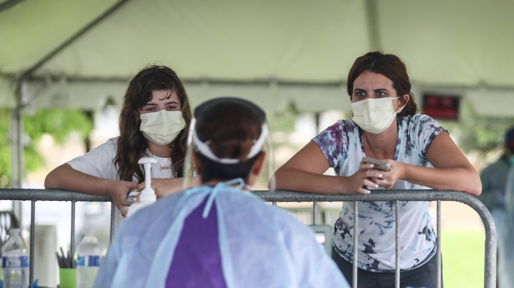 Health care workers take information from Ashley Perez and her daughter Hailey Garcia before they are tested for COVID-19 in a medical tent at a testing site locate at the Miami Lakes Youth Center on