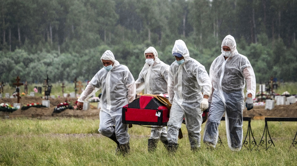 Cemetery workers wearing protective suits carry the coffin of a COVID-19 victim in the special purpose for coronavirus victims section of a cemetery in Kolpino, outside St.Petersburg, Russia, Tuesday,