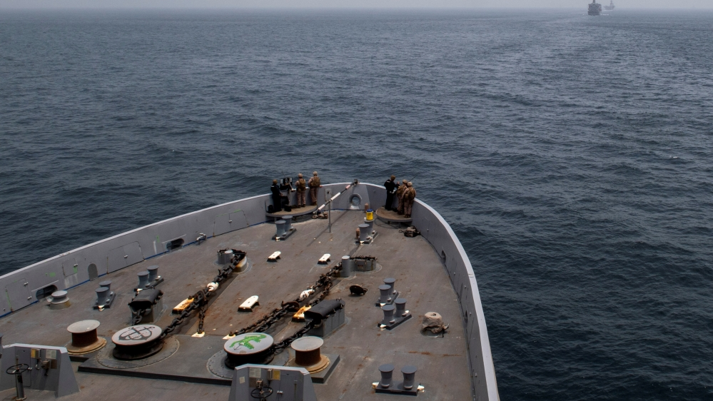 The amphibious transport dock ship USS John P. Murtha is seen behind the fleet replenishment oiler USNS Tippecanoe (T-AO 199) and amphibious assault ship USS Boxer as it transits the Strait of