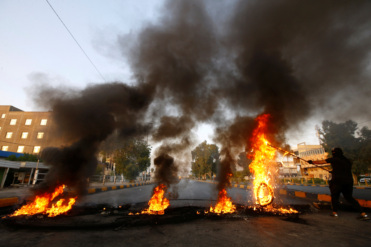Protesters burn tires in the city of Najaf. [Alaa Al-Marjani/Reuters]
