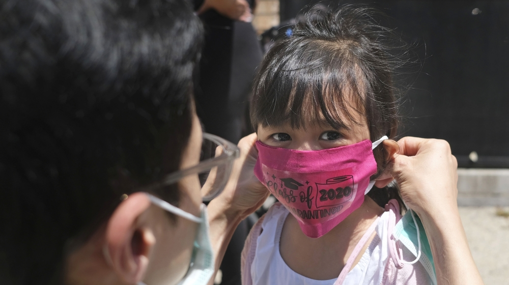 Olivia Chan's father helps her with a new mask she received during a graduation ceremony for her Pre-K class in front of Bradford School in Jersey City, N.J. School districts that plan to reopen class
