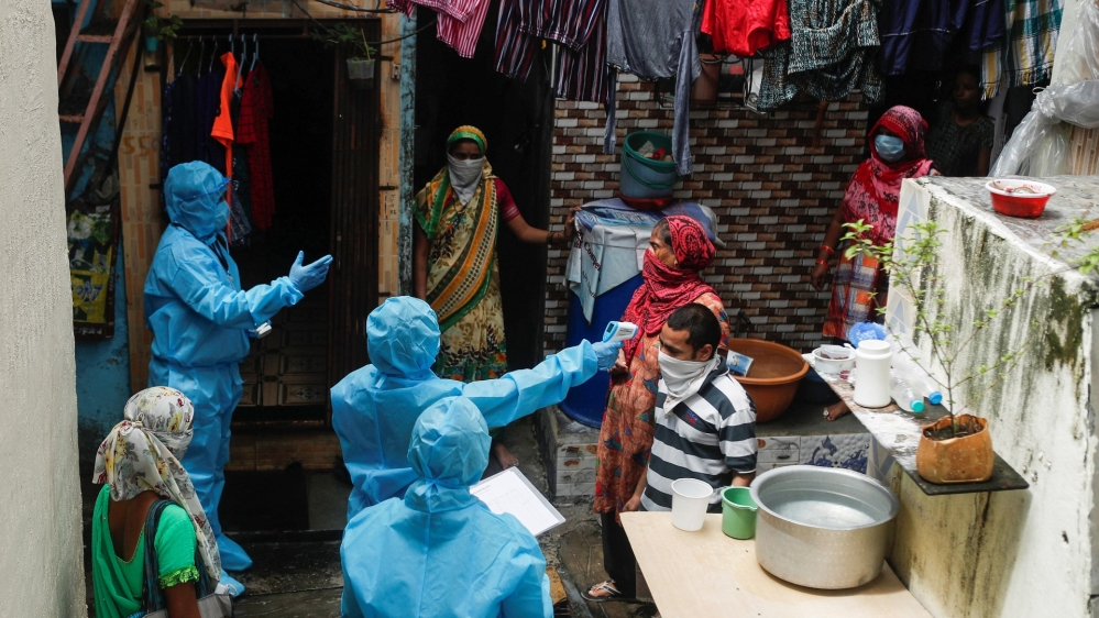 A healthcare worker checks the temperature of a resident during a medical campaign for the coronavirus disease (COVID-19) at a slum area in Mumbai