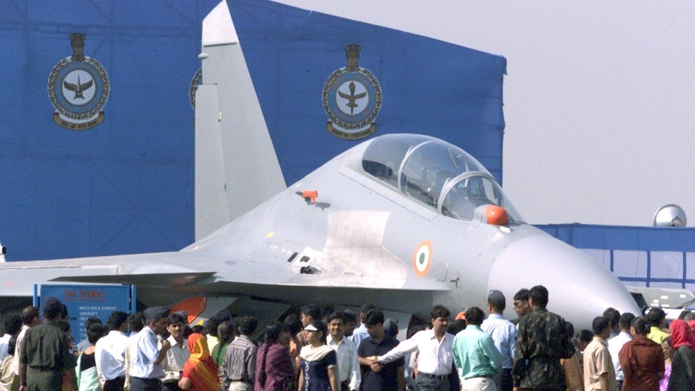 Indian visitors stand besides a SU-30 MKI fighter jet