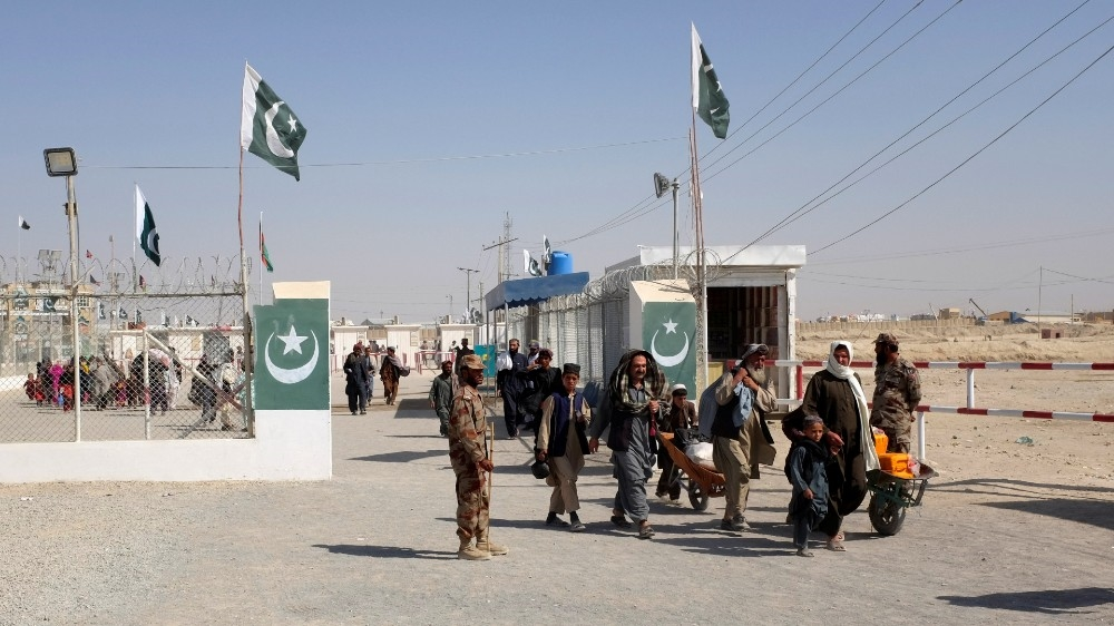 Pakistani soldiers keep guard as citizens return from Afghanistan at the border-crossing town of Chaman