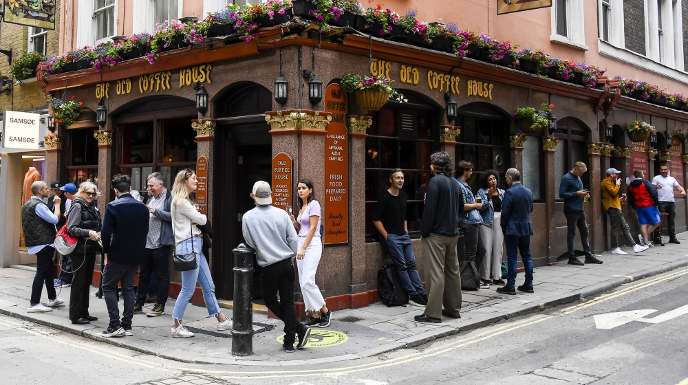 People stand outside a pub in Soho, as the capital is set to reopen after the lockdown due to the Coronavirus outbreak, in London, Saturday, July 4, 2020. England is embarking on perhaps its biggest l