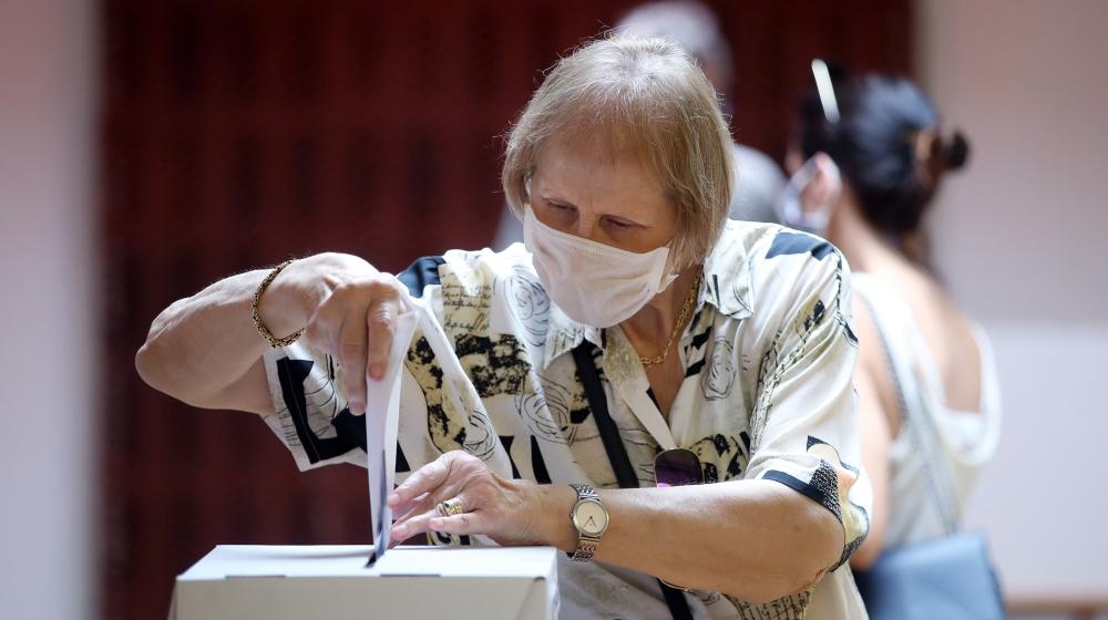 Yüz maskesi takan bir kadın, ülkesinin parlamento seçimleri sırasında 5 Temmuz 2020'de Zagreb'de bir sandık merkezinde oy pusulasını attı. Damir SENCAR / AFP