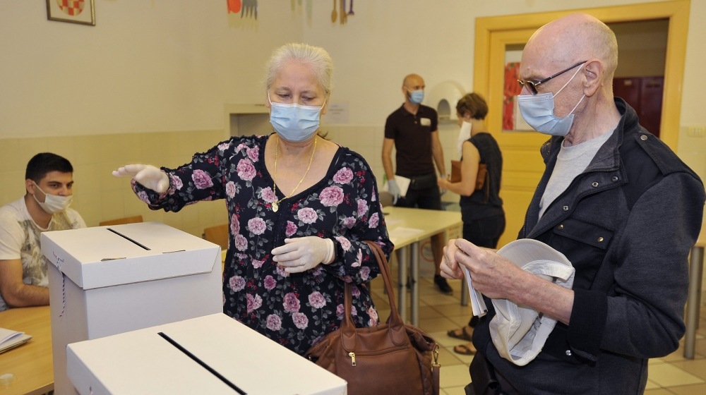 Seçmenler 5 Temmuz 2020 Pazar günü Zagreb, Hırvatistan'daki bir seçim istasyonunda oy pusulaları düzenlediler. Yeni koronavirüs vakalarının ani yükselişinin ortasında Hırvatistan'daki seçmenler Pazar günü yakın bir parli olması bekleniyor