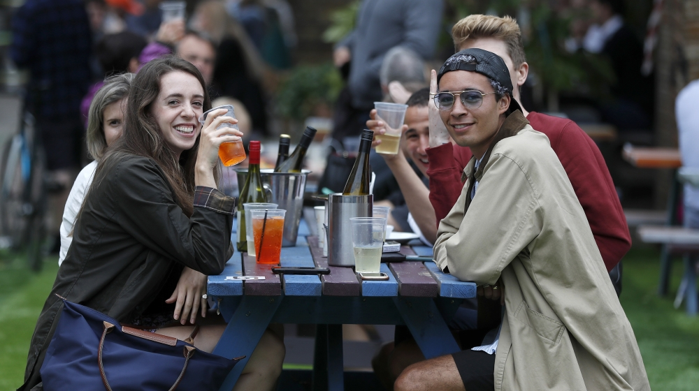 People enjoy their drinks at The Black Lion pub in London, Saturday, July 4, 2020. England is embarking on perhaps its biggest lockdown easing yet as pubs and restaurants have the right to reopen for