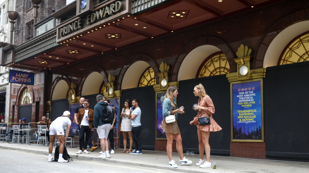 Customers of a bar stand drinking outside the closed Prince Edward theater in London, U.K., on Saturday, July 4, 2020. Restaurants, hotels, cinemas and hairdressers will also be allowed to open their