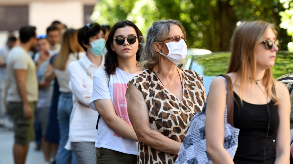 People wearing facemasks and respecting social distancing amid concerns over the COVID-19 coronavirus, wait in front of a polling station before voting for the country's parliamentary elections on Jul