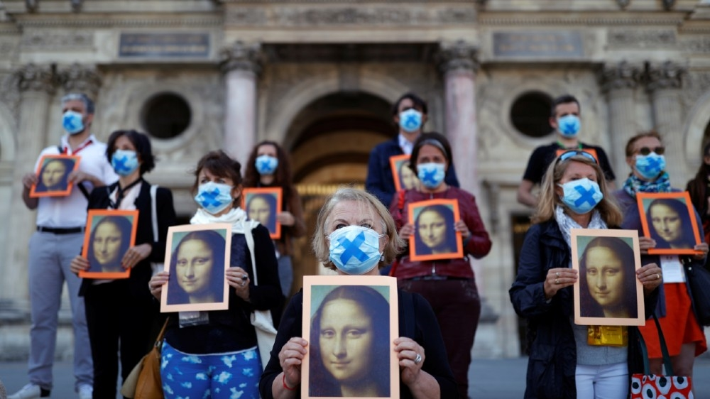 Paris tour guides hold posters depicting Mona Lisa painting by artist Leonardo da Vinci during an action at Le Louvre museum courtyard to warn on their working conditions