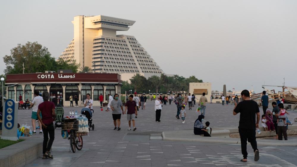 People walk on Doha's corniche as Qatar enters phase two of easing coronavirus  restriction [Sorin Furcoi/Al Jazeera]