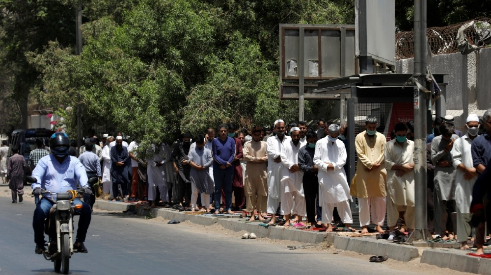 People attend Friday prayers along a sidewalk at a business area, after Pakistani authorities re-imposed lockdowns in selected areas in an effort to stop the spread of