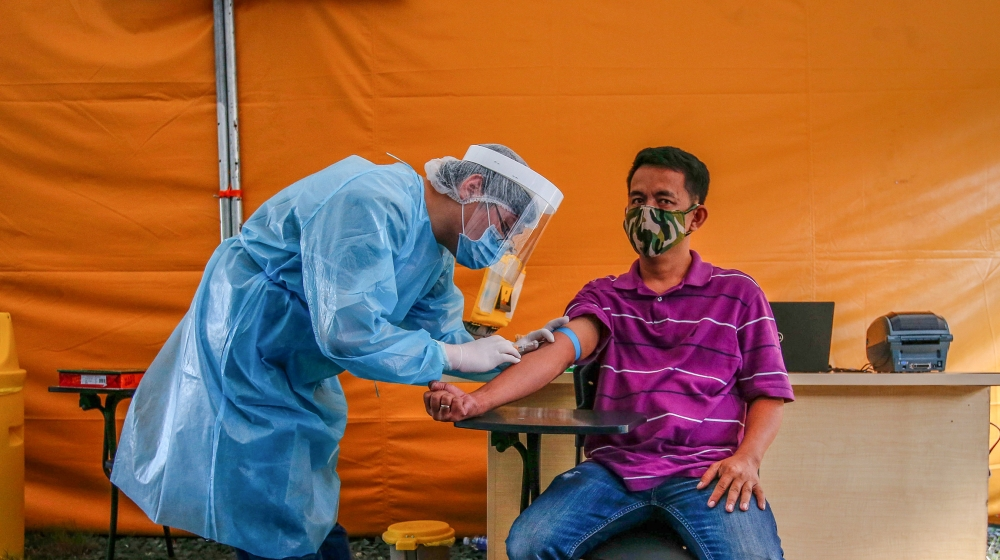 A health worker performs an Enhanced Chemiluminescence Immunoassay (ECLIA) antibody test on a man at a drive-thru COVID-19 testing facility at the Medical City in Ortigas, east of Manila, Philippines,