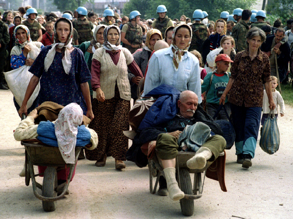 A group of Bosnian Muslim refugees from Srebrenica walks to be transported from eastern Bosnian village of Potocari to Muslim-held Kladanj near Olovo on July 13, 1995. [Reuters]