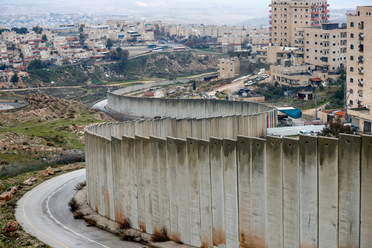 The Israeli settlement of Pisgat Zeev (left), built in a suburb of the mostly Arab East Jerusalem, and the Palestinian Shuafat refugee camp behind Israel's controversial separation wall. [File: Ahmad Gharabli/AFP]
