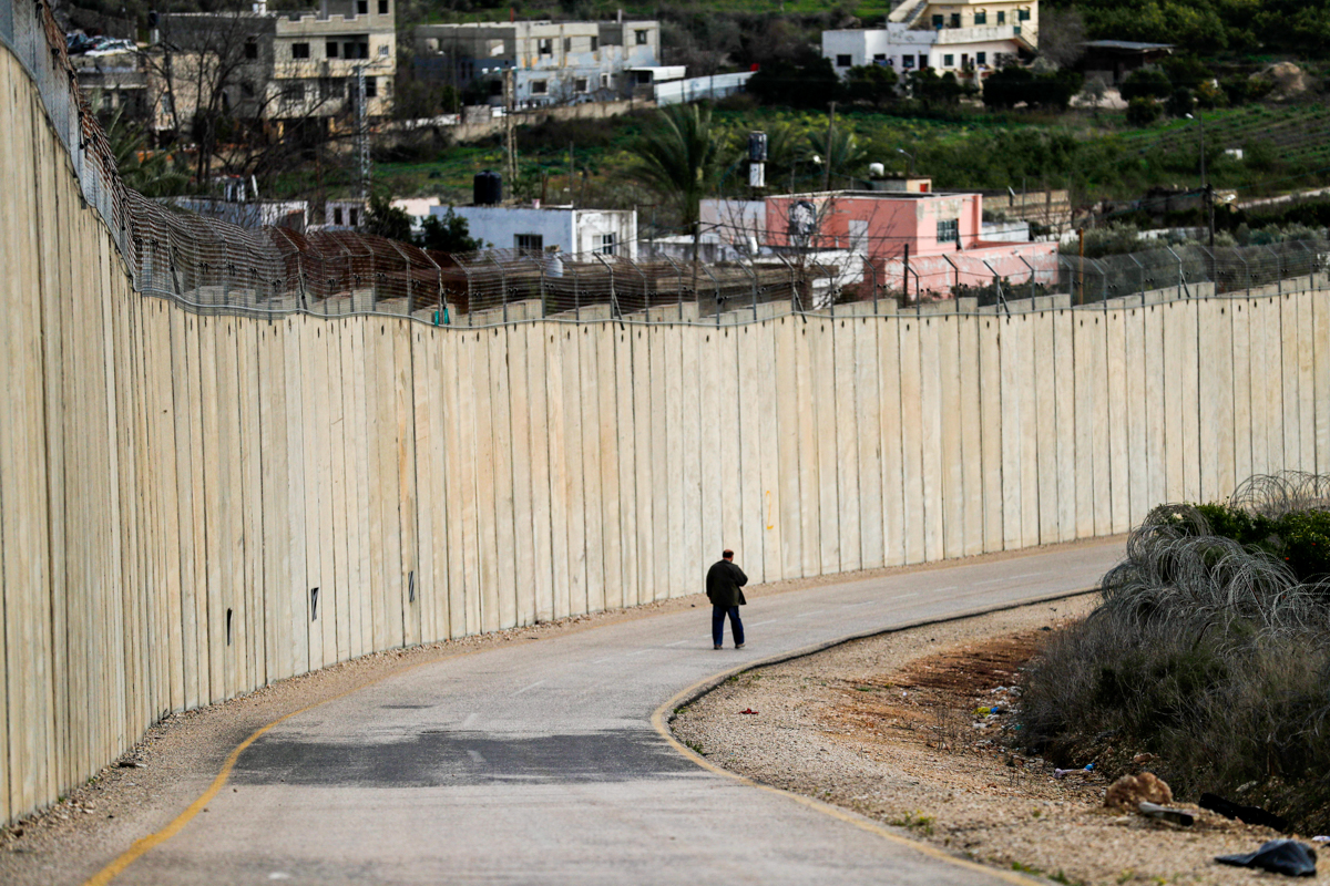 A man walks along a road by Israel's controversial separation barrier between the occupied West Bank village of Nazlat Issa (left) and the Arab-Israeli town of Baqa al-Gharbiya (right) in northern Israel. [File: Ahmad Gharabli/AFP]