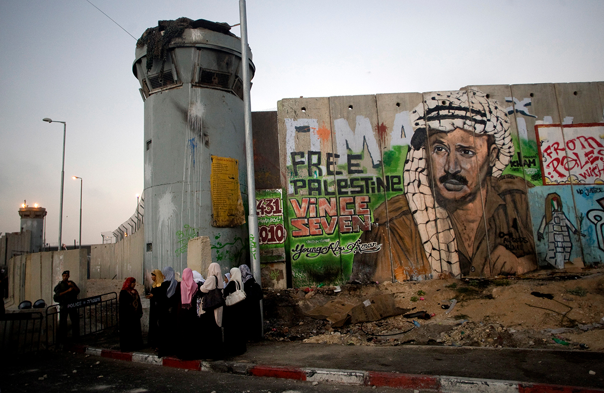 Israel's separation barrier covered in graffiti, one depicting the late Palestinian leader Yasser Arafat at the Qalandiya checkpoint between Jerusalem and the West Bank city of Ramallah. [File: Sebastian Scheiner/AP]