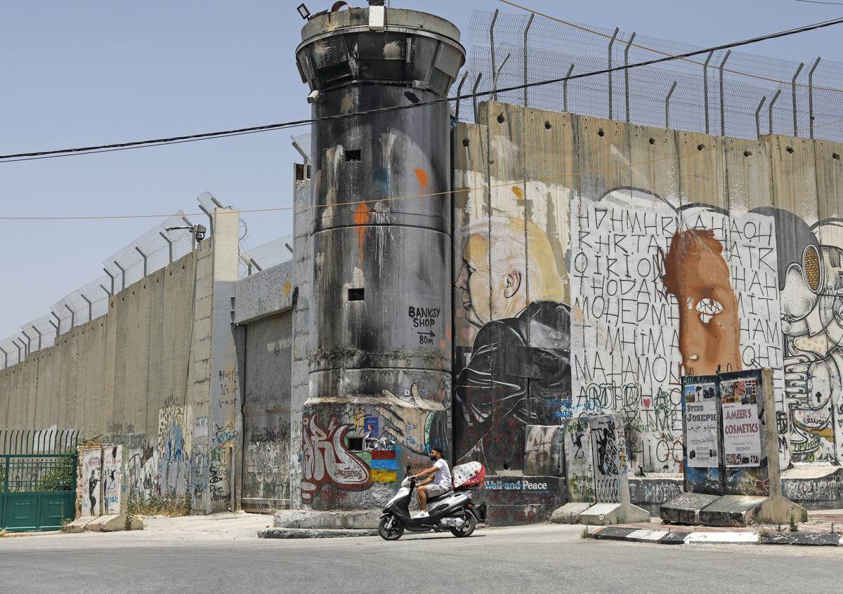 A Palestinian man rides his motorcycle past a mural of US President Donald Trump on Israel's controversial separation barrier in the West Bank city of Bethlehem. [File: Ahmad Gharabli/AFP]