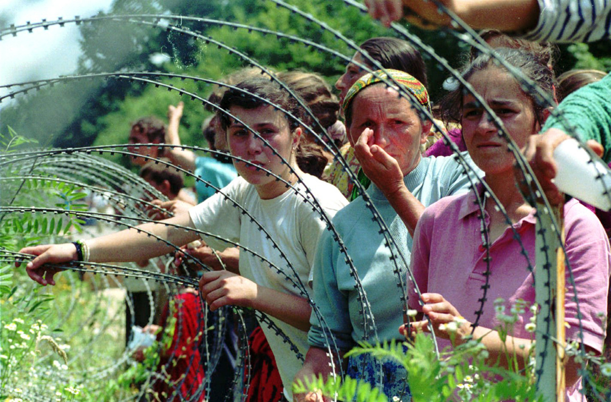 In this July 13, 1995 photo, refugees from the overrun UN enclave of Srebrenica looking through the razor-wire at newly arriving refugees at a UN base in the south of Tuzla, 100km (60 miles) north of Sarajevo. [Darko Bandic/AP Photo]