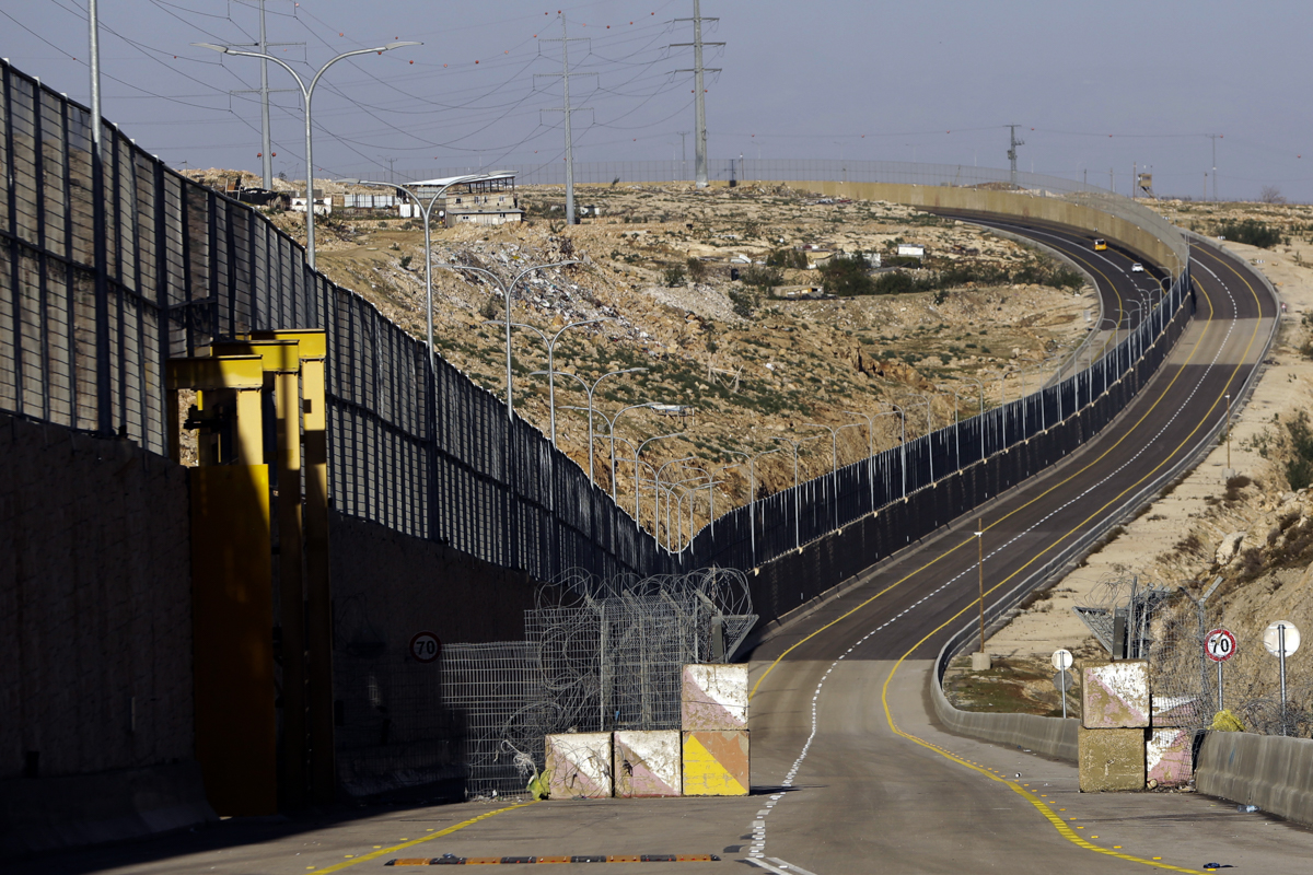 A segregated Israeli highway near Jerusalem that features a large concrete wall segregating Israeli and Palestinian traffic. Critics have branded the road an 'apartheid highway', saying it is part of a planned segregated road system that would benefit Israelis exclusively. [Mahmoud Illean/AP]