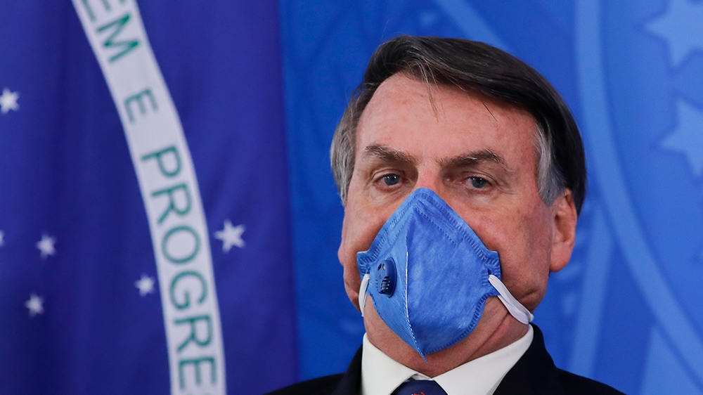 Brazil President Jair Bolsonaro wears a face mask during a press conference on the coronavirus pandemic COVID-19 at the Planalto Palace in Brasilia, Brazil on March 20, 2020. - Brazil's government
