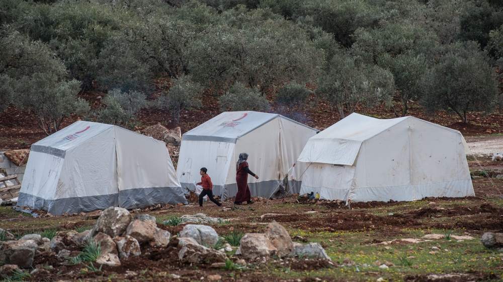 Displaced Syrians walk past their makeshift tents build near olive trees near the village of Atmeh on February 22, 2020 in Idlib, Syria. Turkey's President Recep Tayyip Erdogan in a speech Tuesday thr