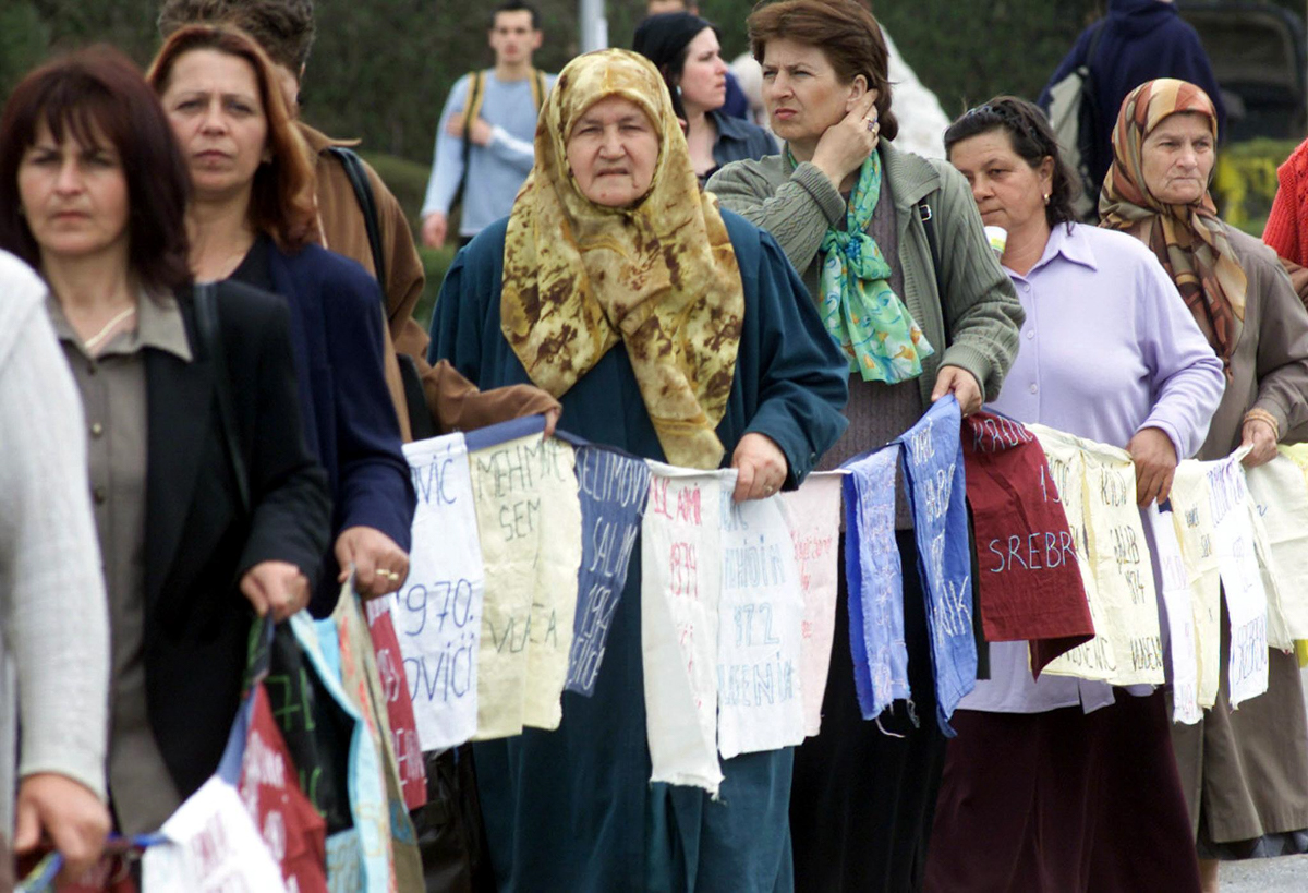Bosnian Muslims, survivors of the 1995 Srebrenica massacre, hold a line of posters with the name of their missing relatives in the central Bosnian town of Tuzla in this April 11, 2003 photo. [AFP]