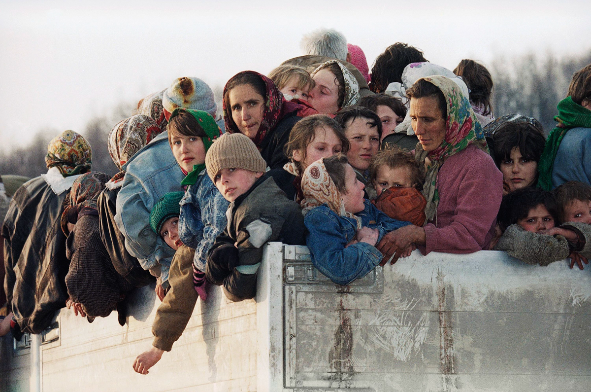 Evacuees from the besieged Muslim enclave of Srebrenica, packed on a truck en route to Tuzla, pass through Tojsici, 90km (56 miles) north of Sarajevo in this March 29, 1993 photo. More than 2,300 evacuees left Srebrenica on UN trucks for Tuzla. [Michel Euler/AP Photo]