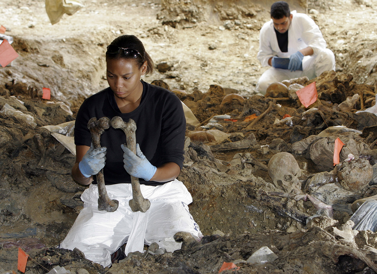 Forensic expert Sharna Daley of London, front left, examines two bones to find out whether they belong to the same person during exhumation at the mass grave site in the village of Kamenica on the outskirts of the eastern Bosnian town of Zvornik, 120 km (74 miles) north of Sarajevo in this July 5, 2006 photo. The mass grave in Kamenica is considered to be a secondary mass grave, where bodies initially buried elsewhere were dumped, and contained bodies of more than 200 people. Most of the remains were believed to be of Muslims from Srebrenica. [Amel Emric/AP Photo]