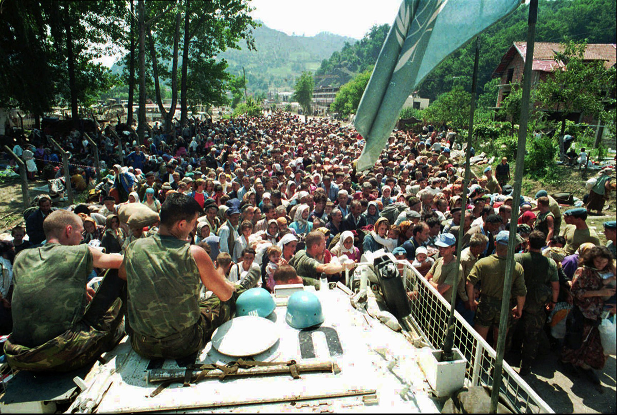 In this July 13, 1995 photo, Dutch UN peacekeepers sit on top of an armoured personnel carrier as Muslim refugees from Srebrenica gather in the nearby village of Potocari. [AP Photo]