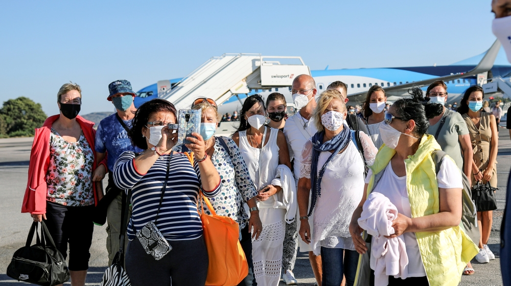 A woman takes a picture of Greek Tourism Minister Harry Theoharis as he welcomes passengers from Germany, who were frontline workers during the coronavirus disease (COVID-19) outbreak, after landing o