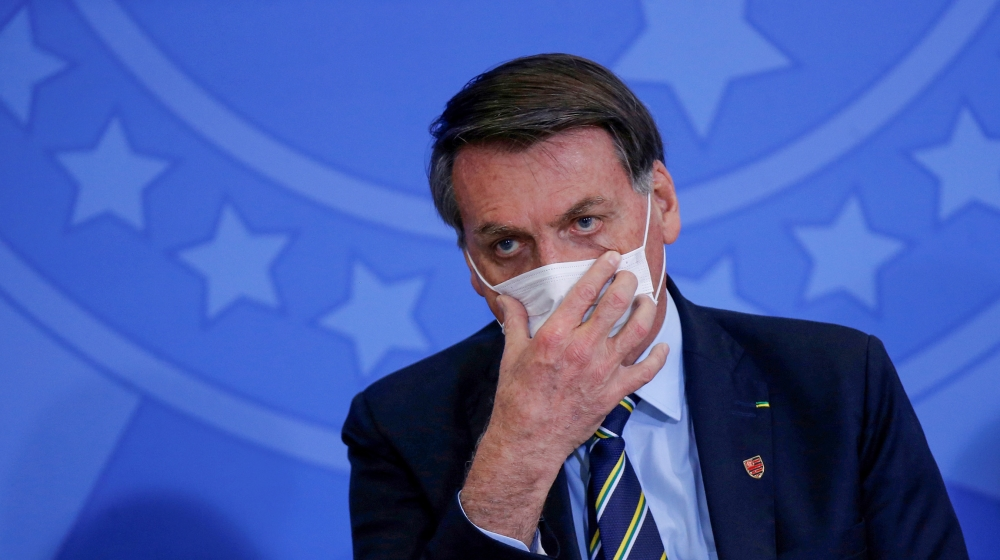 Brazil's President Jair Bolsonaro adjusts his protective face mask during the inauguration ceremony of the new Communications Minister Fabio Faria (not pictured) at the Planalto Palace, in Brasilia, B