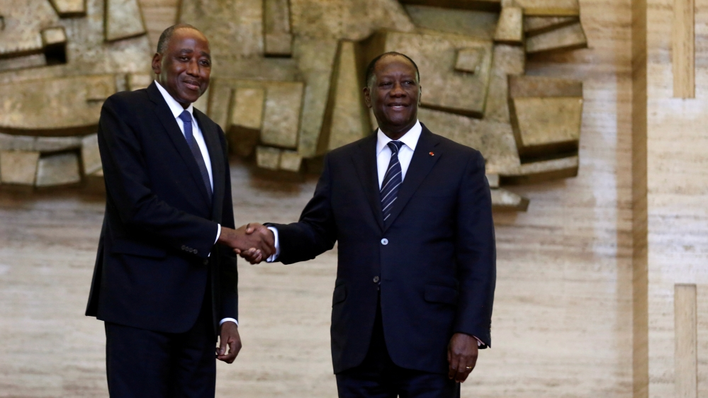 FILE PHOTO: Ivory Coast President Alassane Ouattara and new Prime Minister Amadou Gon Coulibaly pose for pictures in the Presidential Palace in Abidjan