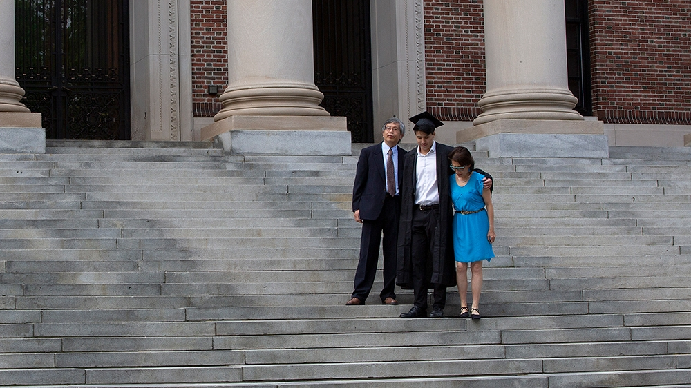 epa08450052 Harvard College Class of 2020 Graduate Tyler Yan (C) along with his parents James Yan (L) Min Chang (R) pose for photo on the stairs of the Widener Library on what would have been the 369t