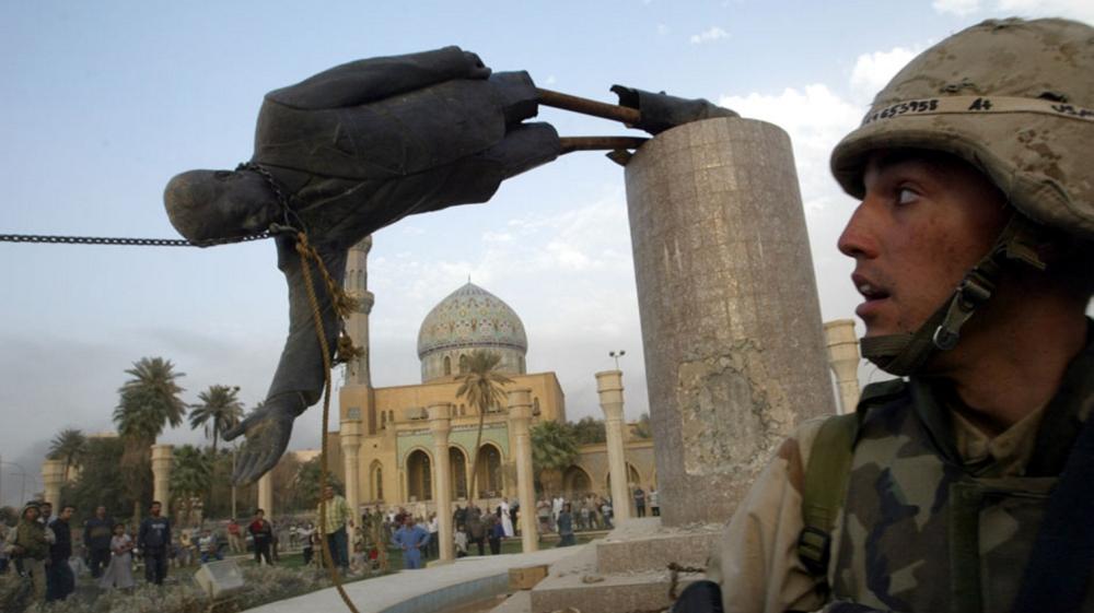 Photo de fichier de l'assaut de la US Marine Corp Kirk Dalrymple regardant une statue du président irakien Saddam Hussein tombe dans le centre de Bagdad