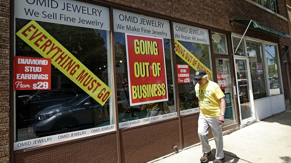 A man walks past a retail store that is going out of business due to the coronavirus pandemic in Winnetka, Ill., Tuesday, June 23, 2020. More than 1.4 million laid-off Americans applied for unemployme